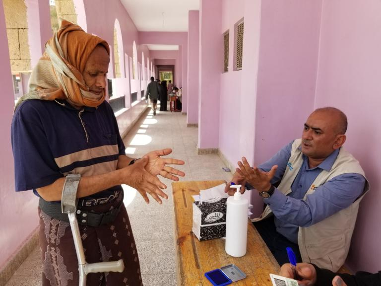 There are hand sanitizers at the main gate, and work with the committees distributing vouchers to people to ensure people sterilize their hands when they come to collect their vouchers and when they leave.  Photo: Nasser Abdulkareem/NRC