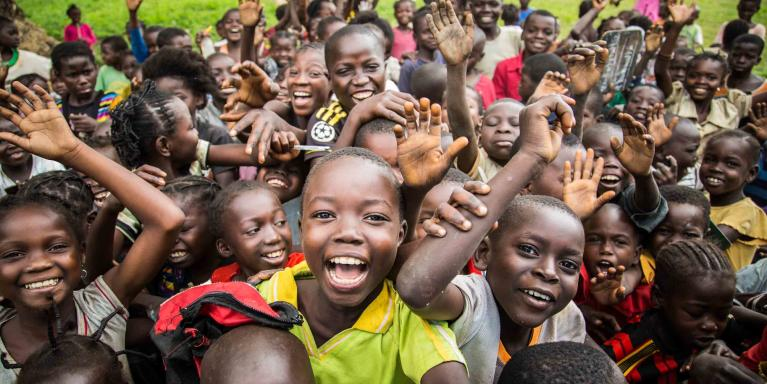 Children in the Central African Republic smiling and waving at the camera.
