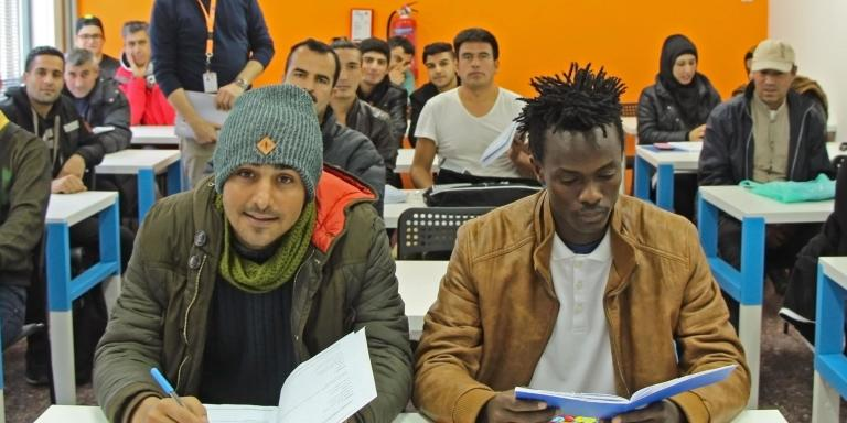 Sekou Kumara (right), 18, sits at the front of his English class in Thessaloniki as teacher Vassilis Papadopoulos looks on. Photo: Maria Gounaridou/NRC