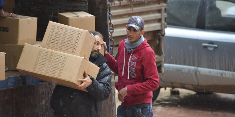 NRC staff offload relief kits from delivery trucks to distribute to families in Hazzeh, Eastern Ghouta. These boxes contain the necessities for everyday use (soap, hygiene items, blankets, mattresses, mats, jerry cans, plastic sheets and a plastic washing basin). Photo: Tareq Mnadili/NRC