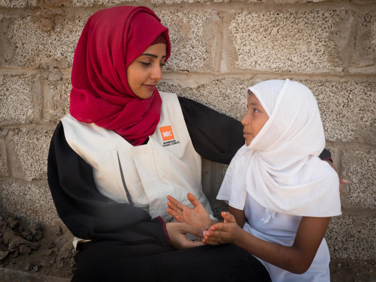 Aden, Yemen. NRC's education assistant Malka Mohammed (26) speaking with a young girl.