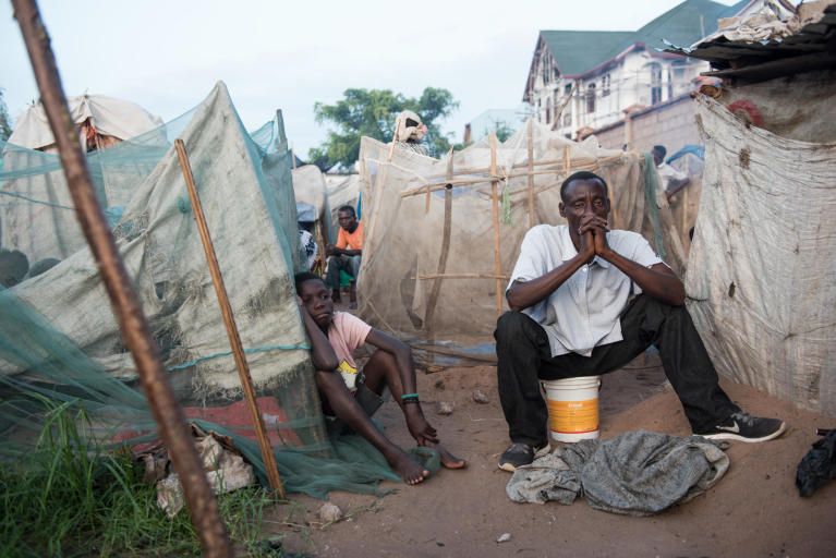 Three internally displaced men sitting in front of make shift shelters in the grounds of Glory Primary School in Kalemie town in the Democratic Republic of the Congo. Photo: NRC/Christian Jepsen
