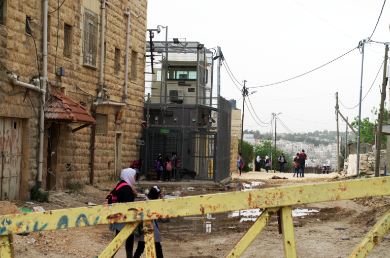 Within 10 meters of the entrance to Muna's apartment building lies the Qafisheh checkpoint. A yellow steel gate, sometimes manned, prevents entry to vehicles.  Photo: Ivan Karakashian/NRC