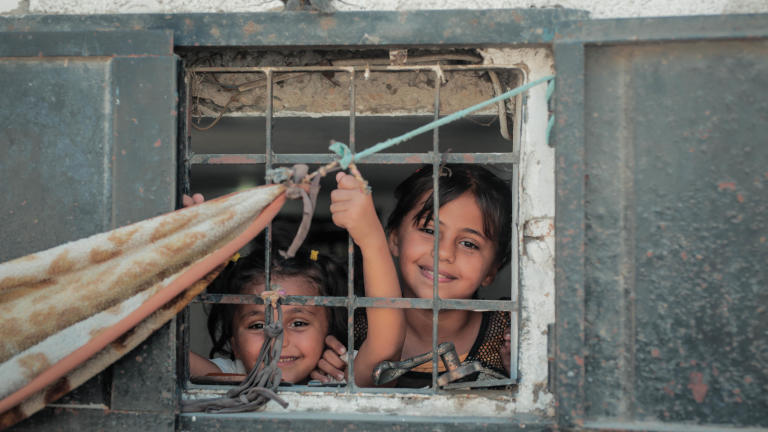 Remas Al-Zaharneh, 7, and her sister Layali, 11, looking from their apartment window. Photo taken on 21 August 2019, Jabalia, northern Gaza. Photo: Ahmed Mashharawi/NRC