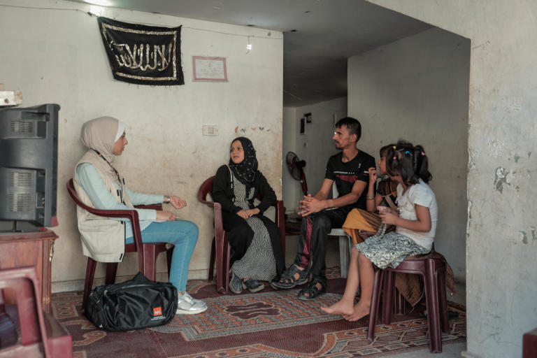 "NRC Shelter Technical Assistant Aya Abu Ramadan (left) meets the Al Zaharna family inside their rented apartment. To her immediate right is Eitidal, 30, her husband Medhat, 33, Remas, 7, and Layali, 11. ""Just before NRC's support, the landlord had warned us that we have a short period to search for another house, as we had four months of unpaid rent,"" said Eitidal. ""We remain worried about what will happen when the six months of cash for rent assistance ends and fear eviction."" Eitidal and her family have been renting their home in Jabalia for the past year. Less than half of households surveyed by NRC have lived in the same place for more than one year, due to their inability to pay rent.  The apartment's poor condition, limited ventilation, mice, and cockroaches are still better than living on the street.  Out of the 522 households, 23 per cent live in homes that fail to meet the minimum standards set by the Shelter Cluster, an inter-agency mechanism that coordinates the humanitarian shelter response, while 4 per cent live in informal shelters such as storage units, which lack even running water and sanitation. The family has been evicted twice before over accumulated rental debts. Their previous landlord cut off their electricity, threw their furniture out on the street, and submitted a complaint to the police.  Too often, Eitidal says, she finds herself without food for her children. In May, her daughter, Rimas, tired and hungry after school exams, ate leftover food thrown away by a nearby restaurant, and had a nasty bout of food poisoning. Since hearing of the story, the restaurant owner has given the family cooked rice for free, and whenever Eitidal has nothing to feed her kids, she sends them there to eat. Other times, Eitidal's husband brings home spoiled vegetables from the market and every once in a while they go over to their relatives for meals.   Even drinking water can be hard to come by.  ""We do not have either a water tank or a jerry can,"" said Eitidal. ""I send my daughters to the supermarkets to fill 10 water bottles at a cost of one shekel [US$0.28]. Sometimes we do not have one shekel and must hope on the goodwill of neighbours."" According to the 2018 food security survey by the Palestinian Central Bureau of Statistics, 68.5 per cent of Gaza's households are food insecure, with 47 per cent severely affected.     Eitidal's family receives cash assistance of 1,000 NIS (US$284) from the Ministry of Social Development every six months and UNRWA food vouchers every three months. Eitidal has had to sell the food items she purchases with these vouchers for half their worth to have money for medicine, gas, and other basic necessities. Otherwise, they rely on the goodwill of relatives and strangers to survive. Around six months ago, Eitidal, in desperate need of money, promised the same food items she was due to receive to two people. When she was unable to provide the second person with the items, he made a complaint to the police.   ""The police came to take my husband to jail, and my daughters started to cry,"" said Eitidal. ""Since then, they have become terrified every time they see a police officer.""  Eitidal's husband spent 21 days behind bars.  More recently, Eitidal signed a promissory note (a promise to pay outstanding debts by a fixed date) for debts in the amount of 220 NIS (US$63) to a supermarket owner, who involved the police to force the family to pay the full amount in installments.   ""The day we receive the cash assistance from the Ministry of Social Development is the worst ever,"" said Eitidal. ""All the lenders come asking for their money."" Photo taken on 21 August 2019, Jabalia, northern Gaza. Photo: Ahmed Mashharawi/NRC"