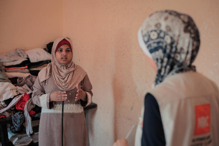 Diana Murad, 18 – Jumana's oldest daughter – seen here talking to NRC shelter assistant Aya Abu Ramadan in her family's rented apartment. Diana sustained shrapnel wounds to her left arm and thigh in 2018 while taking part in the Great March of Return mass protests on Fridays along Gaza's perimeter fence with Israel. In March this year, a tear gas canister struck her in the right shoulder. While Diana's father looked for her amid the crowds, he fell to the ground with a bullet wound to the leg. Complications arising from diabetes and kidney problems have stalled his recovery. Photo taken on 21 August 2019 Photo: Ahmed Mashharawi/NRC