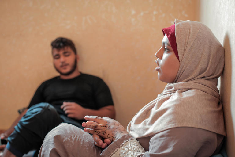 Diana Murad, 18, and her brother Mohammed, 15, in the background in their rented apartment in Al Shati Refugee Camp in Gaza City. Diana sustained shrapnel wounds to her left arm and thigh in 2018 while taking part in the Great March of Return mass protests on Fridays along Gaza's perimeter fence with Israel. In March this year, a tear gas canister struck her in the right shoulder. While Diana's father looked for her amid the crowds, he fell to the ground with a bullet wound to the leg. Complications arising from diabetes and kidney problems have stalled his recovery. All five siblings dropped out of school because of the number of times they have been forced to move after getting evicted from their home, as well as lack of funds for school fees, uniforms, and transportation. Ali and Mohammad, 15, completed first grade only; their siblings Jenin, 17, and Saed, 16, made it to second grade, and Diana graduated from fifth grade. Photo taken on 21 August 2019 Photo: Ahmed Mashharawi/NRC